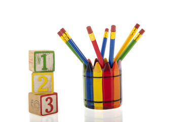 Collage of colourfull pencils in a cup next to three 1-2-3 cubes