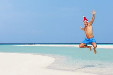 Man Jumping On Beach Wearing Santa Hat