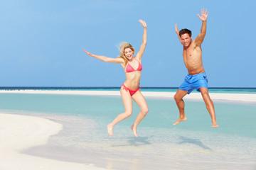 Couple Jumping On Beautiful Tropical Beach