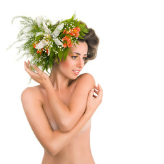A beautiful naked girl with flowers on her head on a white backg