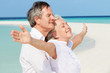 Senior Couple Withs Arms Outstretched On Beautiful Beach