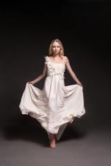 Dancing girl in wedding dress over dark background