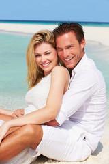 Romantic Couple Sitting On Beautiful Tropical Beach
