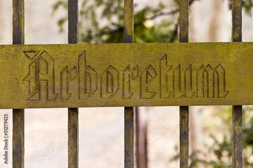 Holzschild - Arboretum - an einem Metallzaun