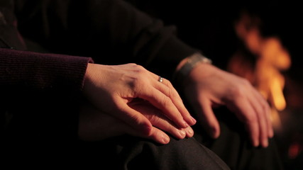 Close up of a couple holding hands in front of a fire