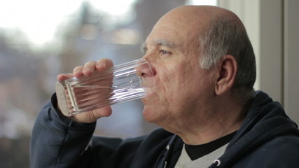 Man drinking water near window