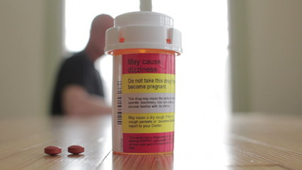 Prescription bottle with man in the background