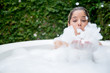 Happy woman taking a bubble bath