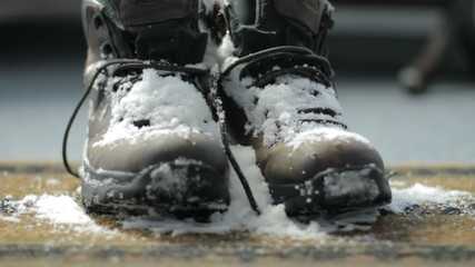 A pair of snowy boots dropped on a welcome mat