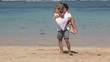 Happy woman jumping on boyfriend and spinning together at beach