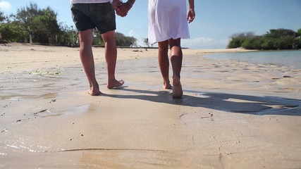 Couple feet walking on sand while tropical vacation Bali