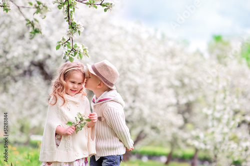 Two young children kissing in flowery meadow of long grass, bloo