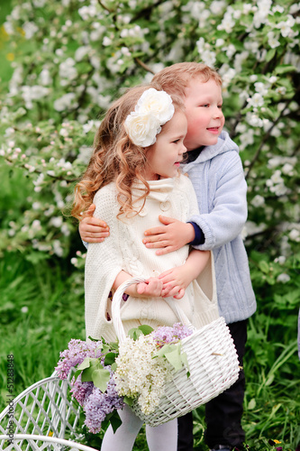 Two young children  in flowery meadow of long grass