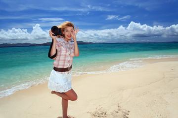南国沖縄の美しいビーチで撮影を楽しむ笑顔の女性