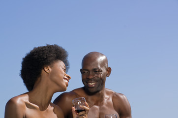Happy mixed African couple against a blue sky.