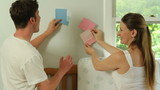 A young couple looks at paint swatches.