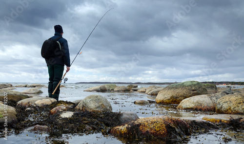 Lonely angler on spring sea coast