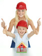 Two girls with helmet shows thumbs up for building a house
