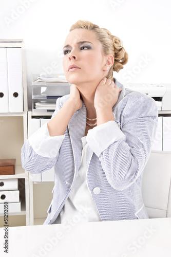 Frau im Büro hat Nackenschmerzen