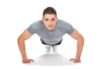 muscle model guy making push ups exercise over gray background.