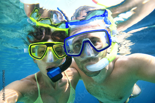 Woman and man doing snorkeling in the blue sea