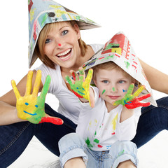 Mother and her son have a lot of fun to paint with colours