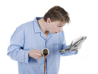 Man reading morning newspaper and is astonished or afraid