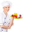 Joyful woman cook in chefs cap with pure vegetables on plate