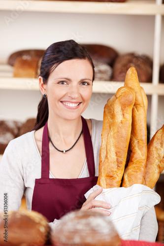 lächelnde verkäuferin mit baguettes