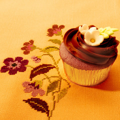 delicious chocolate cupcake on vintage tablecloth