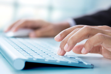 Business hand touching computer keys during work