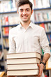 Portrait of a smiling male student holding a book in a library