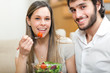 Loving happy couple eating salad in the kitchen - indoors