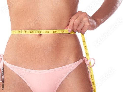 Young slim woman measuring her waist with a tape