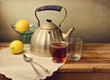 Vintage teapot with lemons and tea on wooden table