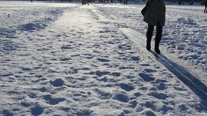 woman slide frozen ice field lake winter evening sulight shadows