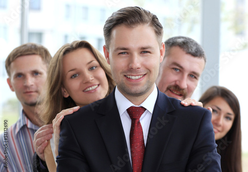 happy young male business leader standing in front of his team