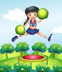 A cheerleader jumping with her green pompoms above a trampoline