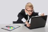 Angry schoolboy with laptop, on gray background