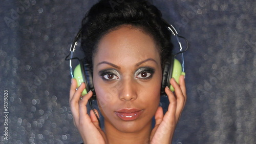 Young woman listens to headphones. Stop action effect.