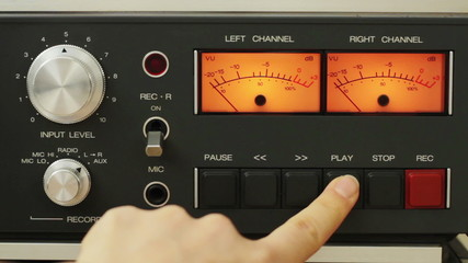 Finger pushing the play and stop button on vintage tape recorder