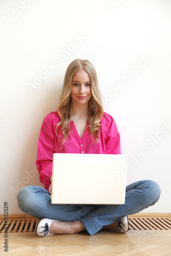 Young woman with laptop sitting on the floor