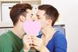 Schwules Paar küsst sich hinter einem rosa Herz