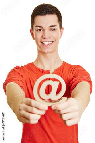 Mann hält at-Zeichen als Symbol für Internet