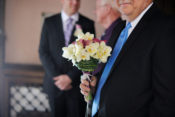 Bride's father holding daughter's wedding bouquet