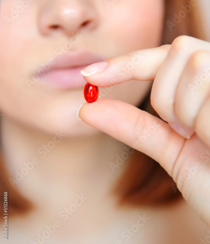 Young woman taking the pill. Focus is on a pill