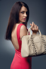 Stylish beautiful woman wearing red dress holding handbag