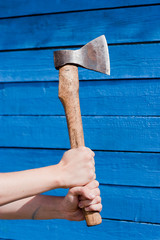 hand with axe on blue wooden background