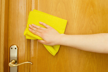 hand cleaning a door with a yellow cloth