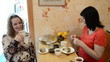 Two pregnant women drink tea with cake